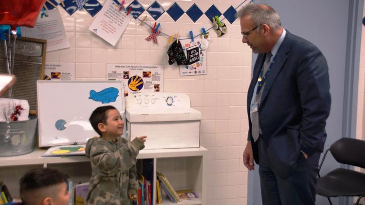 School District U46 CEO Tony Sanders speaks with a young boy at the first Language in the Laundromat site, which opened this spring at JetXpress Laundry on Dundee Avenue in Elgin. (School District U46)